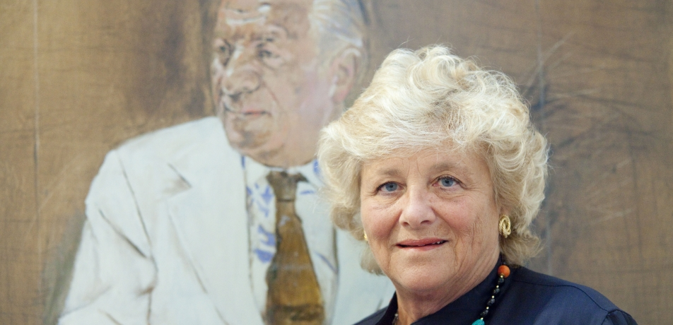 Dame Vivien Duffield stands in front of a portrait of her father, Sir Charles Clore.